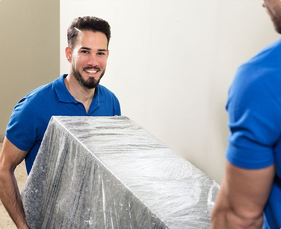 Two Young Male Movers in UniformCarrying Furniture on Staircase
